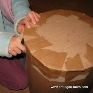 Utilisation du scotch gommé sur un tabouret en carton